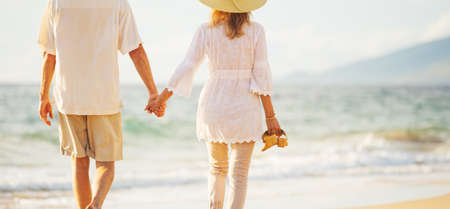 Happy Romantic Middle Aged Couple Enjoying Beautiful Sunset Walk on the Beach Holding Hands Standard-Bild