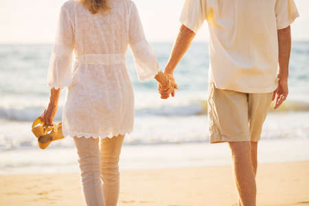 Happy Romantic Middle Aged Couple Enjoying Beautiful Sunset Walk on the Beach Holding Hands Archivio Fotografico
