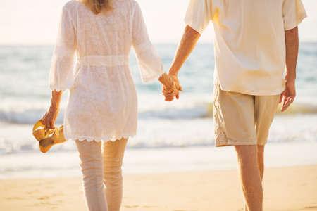 manos sosteniendo: Rom�ntica feliz pareja de mediana edad Disfrutando del sol hermosa caminata en la playa Agarrados de la mano