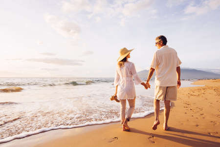 Happy Romantic Middle Aged Couple Enjoying Beautiful Sunset Walk on the Beach. Travel Vacation Retirement Lifestyle Concept Imagens - 49643698