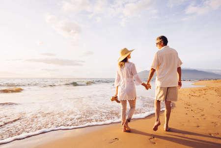 ancianos caminando: Rom�ntica feliz pareja de mediana edad Disfrutando del sol hermosa caminata en la playa. Vacaciones Viaje de Retiro Lifestyle Concept