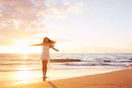 siluetas mujeres: Feliz mujer bailando sin preocupaciones al atardecer en la playa. Concepto de estilo de vida libre feliz. Foto de archivo