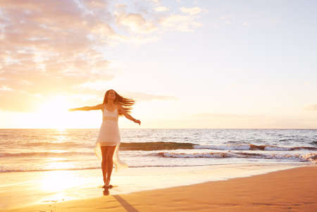nature: Happy carefree woman dancing at sunset on the beach. Happy free lifestyle concept.