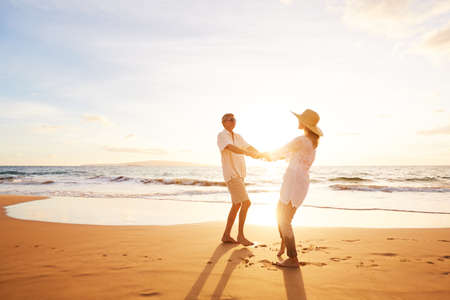 Happy Romantic Middle Aged Couple Enjoying Beautiful Sunset on the Beach. Travel Vacation Retirement Lifestyle Concept. Stock Photo