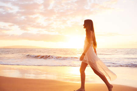 sunrise ocean: Happy Carefree Woman Enjoying Beautiful Sunset on the Beach Stock Photo