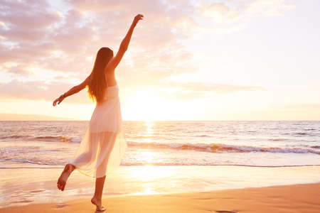 Happy carefree woman dancing at sunset on the beach. Happy free lifestyle concept.