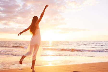 donna che balla: Felice donna ballare spensierata al tramonto sulla spiaggia. Felice concetto di stile di vita libero.
