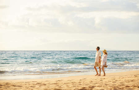 romantic beach: Happy Romantic Middle Aged Couple Enjoying Beautiful Sunset Walk on the Beach. Travel Vacation Retirement Lifestyle Concept