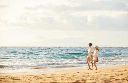 parejas caminando: Rom�ntica feliz pareja de mediana edad Disfrutando del sol hermosa caminata en la playa. Vacaciones Viaje de Retiro Lifestyle Concept