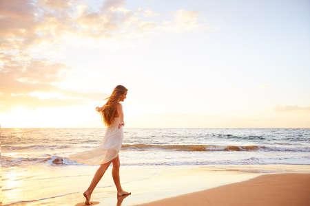 ビーチのサンセットで踊る幸せな屈託のない女。幸せな自由なライフ スタイルのコンセプトです。