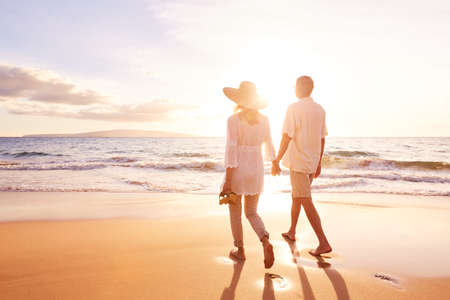 Happy Romantic Middle Aged Couple Enjoying Beautiful Sunset Walk on the Beach. Travel Vacation Retirement Lifestyle Concept. Stock Photo