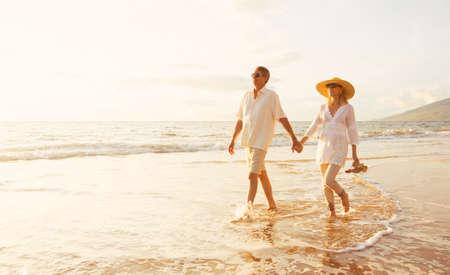 parejas: Romántica feliz pareja de mediana edad Disfrutando del sol hermosa caminata en la playa. Vacaciones Viaje de Retiro Lifestyle Concept