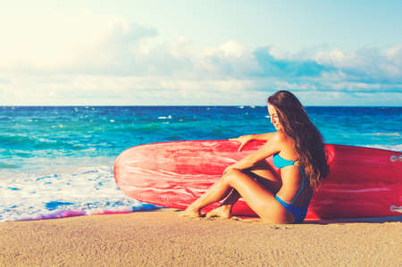 Beautiful Surfer Girl on the Beach at Sunset. Summer Fun Outdoor Lifestyle.