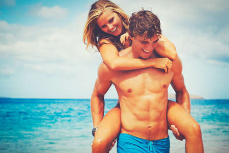 Pares novos atrativos felizes na praia tropical Banco de Imagens