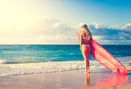 Beautiful Blonde Surfer Girl on the Beach at Sunset. Summer Lifestyle.