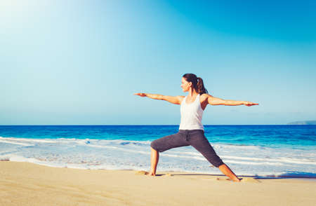 Healthy Lifestyle Concept, Beautiful young woman stretching practicing yoga on the beach Reklamní fotografie