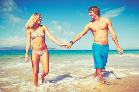 bikini couple: Happy Attractive Young Couple on Tropical Beach Stock Photo