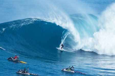 jaws: MAUI, HI - JANUARY 16 2016: Professional surfer Joao Marco Maffini rides a giant wave at the legendary big wave surf break known as Jaws on one the largest swells of the year.