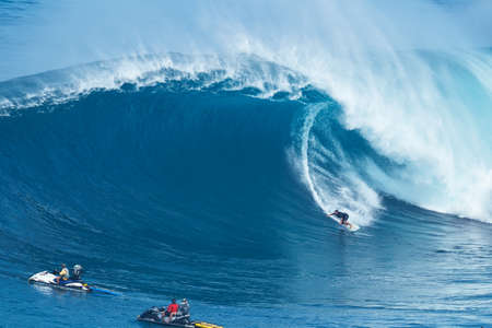 jaw: MAUI, HI - JANUARY 16 2016: Professional surfer Joao Marco Maffini rides a giant wave at the legendary big wave surf break known as Jaws on one the largest swells of the year.