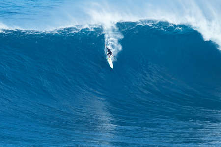 MAUI, HI - JANUARY 16 2016: Professional surfer Joao Marco Maffini rides a giant wave at the legendary big wave surf break known as Jaws on one the largest swells of the year.