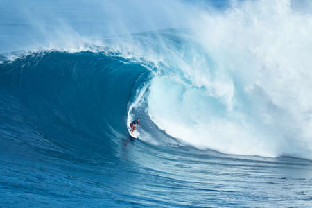 male surfer: MAUI, HI - JANUARY 16 2016: Professional surfer Francisco Porcella rides a giant wave at the legendary big wave surf break known as Jaws on one the largest swells of the year.