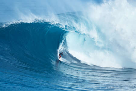 swells: MAUI, HI - JANUARY 16 2016: Professional surfer Francisco Porcella rides a giant wave at the legendary big wave surf break known as Jaws on one the largest swells of the year.
