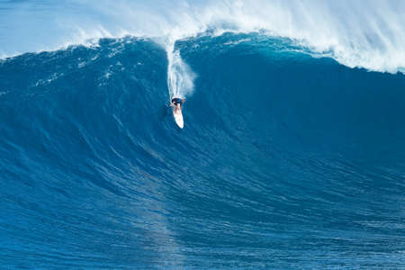 wave: MAUI, HI - JANUARY 16 2016: Professional surfer rides a giant wave at the legendary big wave surf break known as Jaws on one the largest swells of the year.