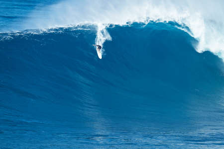 MAUI, HI - JANUARY 16 2016: Professional surfer Ian Walsh rides a giant wave at the legendary big wave surf break known as Jaws on one the largest swells of the year. 新聞圖片