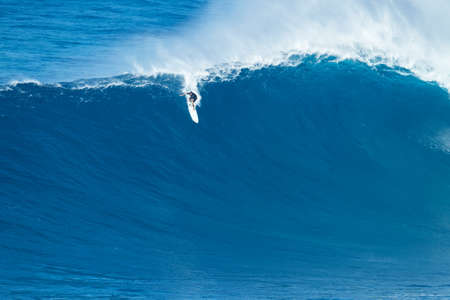 """MAUI, HI - JANUARY 16 2016: Professional surfer Ian Walsh rides a giant wave at the legendary big wave surf break known as """"Jaws"""" on one the largest swells of the year."""