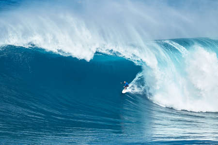 jaws: MAUI, HI - JANUARY 16 2016: Professional surfer Shane Dorian rides a giant wave at the legendary big wave surf break known as Jaws on one the largest swells of the year.