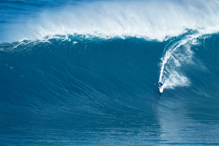 MAUI, HI - JANUARY 16 2016: Professional surfer Shane Dorian rides a giant wave at the legendary big wave surf break known as Jaws on one the largest swells of the year.