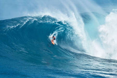 jaws: MAUI, HI - JANUARY 16 2016: Professional surfer Tyler Larronde rides a giant wave at the legendary big wave surf break known as Jaws on one the largest swells of the year.