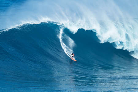 MAUI, HI - JANUARY 16 2016: Professional surfer Tyler Larronde rides a giant wave at the legendary big wave surf break known as Jaws on one the largest swells of the year.