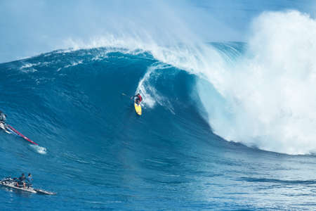 jaws: MAUI, HI - JANUARY 16 2016: Professional surfer Kai Lenny rides a giant wave at the legendary big wave surf break known as Jaws on one the largest swells of the year. Editorial