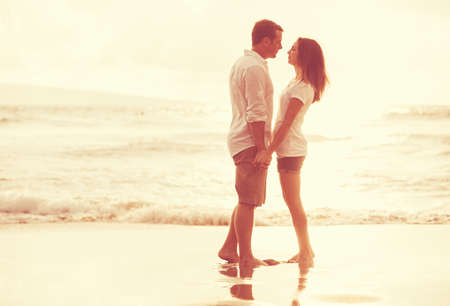 Happy romantic couple on the beach at sunset. Young lovers on vacation.