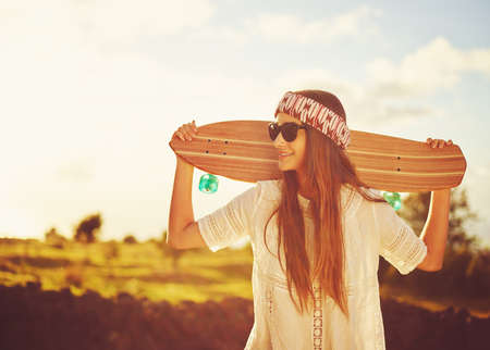 Beautiful young woman with skateboard on country road at sunset