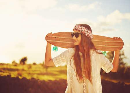Mooie jonge vrouw met skateboard bij de landweg bij zonsondergang
