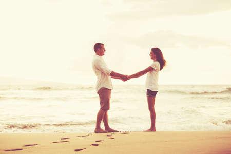 Gelukkig romantisch koppel op het strand bij zonsondergang. Jonge geliefden op vakantie.