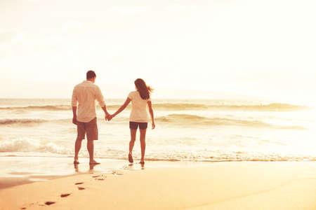 Šťastný romantický pár na pláži při západu slunce. Mladí milenci na dovolenou.