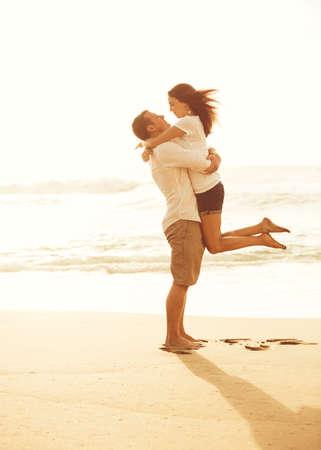 Gelukkig romantisch koppel op het strand bij zonsondergang. Jonge geliefden op vakantie. Stockfoto - 56006820