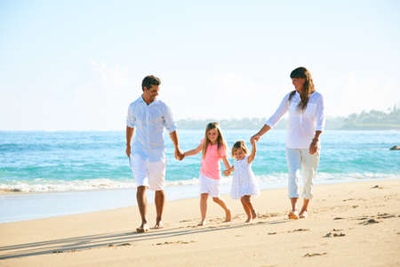 Happy family enjoying walk on the beach Reklamní fotografie - 89519807