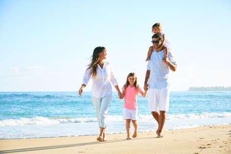 Gelukkige familie die van gang op het strand geniet Stockfoto