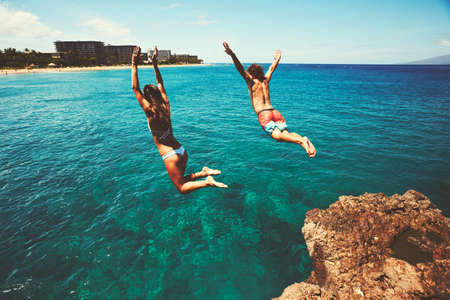 Cliff jumping into the ocean, summer fun adventure lifestyle Reklamní fotografie