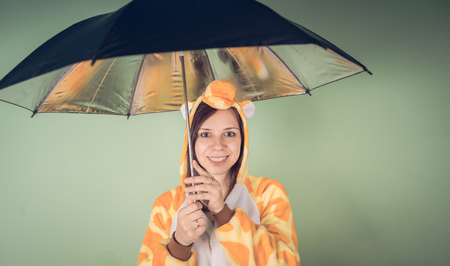 Girl with umbrella in a bright children's pajamas in the form of a kangaroo. emotional portrait of a student. costume presentation of children's animator. Slippers in the form of cat's paws. Banco de Imagens
