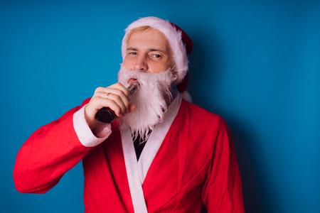 Guy dressed as Santa Claus vaping electronic cigarette closeup. Man smoking e-cigarette to quit tobacco. Vapor and alternative nicotine free smoking concept, copy space