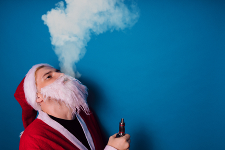 Guy dressed as Santa Claus vaping electronic cigarette closeup. Man smoking e-cigarette to quit tobacco. Vapor and alternative nicotine free smoking concept, copy space