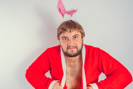 Emotional fat man with a beard. in a red coat with Bunny ears. isolated on white Stock Photo