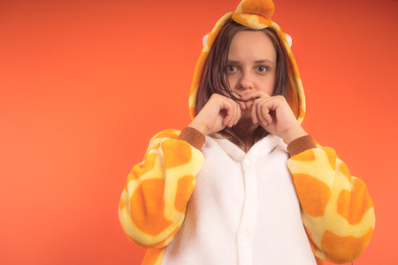 pajamas in the form of a giraffe. emotional portrait of a girl on an orange background. crazy and funny woman in a suit. animator for childrens parties Banque d'images