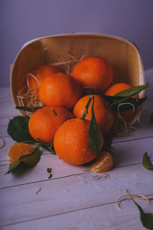 Fresh tangerines on a wooden background. Mandarins with copy space for text. Ripe and tasty tangerines. Clementines on a wooden table. Background tangerines. Stock Photo