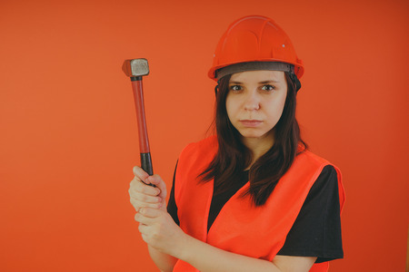 Girl Builder with hammer in hand, concept: girl doing repairs. An image of a road worker or surveyor
